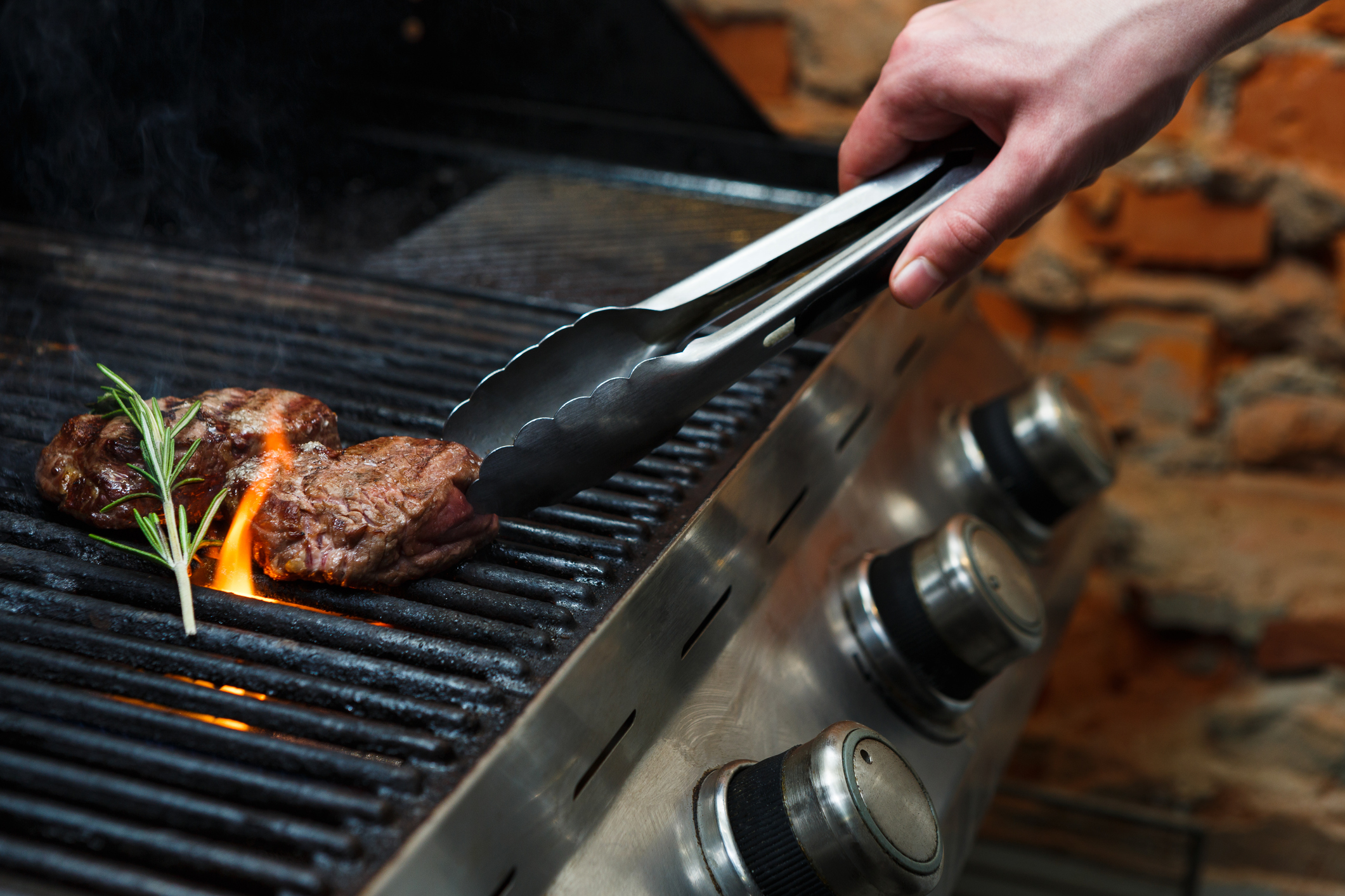 Person grilling meat on an outdoor grill